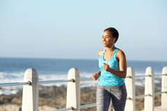 Active young woman running by sea with earphones Stock Images