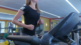 Active young woman running on treadmill in sport club stock video footage