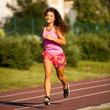 Active young woman runs on atheltic track on summer afternoon.  Royalty Free Stock Image