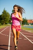 Active young woman runs on atheltic track on summer afternoon.  Stock Photos