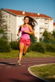 Active young woman runs on atheltic track on summer afternoon.  Stock Photography