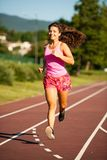 Active young woman runs on atheltic track on summer afternoon.  Royalty Free Stock Photography