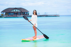Active young woman on stand up paddle board Stock Photos