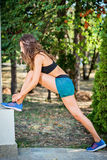 Active young woman streching and doing exercise in a park. Fit f Royalty Free Stock Image