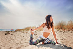 Active young woman streching and practicing exercise on the beac royalty free stock image
