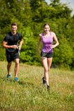 Active young youple running cross country in nature on a fores royalty free stock photo