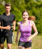 Active young youple running cross country  in nature on a fores. Active young youple running in nature on a fores path Royalty Free Stock Images