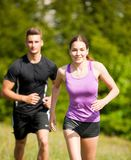 Active young youple running cross country  in nature on a fores. Active young youple running in nature on a fores path Royalty Free Stock Image