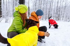 Activefamily walk the dog in the winter forest. Royalty Free Stock Photos
