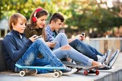Activeteens jouant sur des smarthphones et écoutant la musique Photographie stock libre de droits