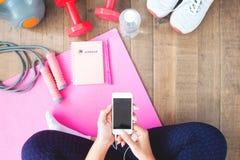 activewear的妇女使用移动设备 与聪明的家庭锻炼 免版税库存照片