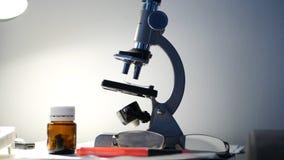 Actividad de investigación en un laboratorio con las píldoras médicas del extremo del microscopio en la tabla fotografía de archivo