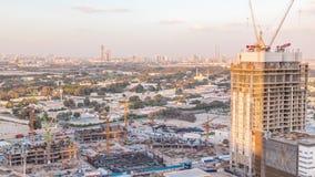 Actividad de la construcción en el centro de la ciudad de Dubai con el timelapse de las grúas y de los trabajadores, UAE almacen de metraje de vídeo