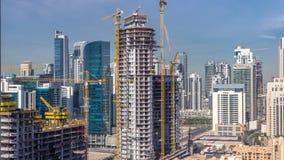 Actividad de la construcción en el centro de la ciudad de Dubai con el timelapse de las grúas y de los trabajadores, UAE metrajes