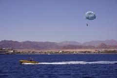 Actividad de la playa: el parasailing, barco de alta velocidad tira de un hombre en un paracaídas Mar y montañas en el fondo fotografía de archivo