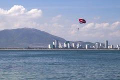 Actividad de la playa: el parasailing, barco de alta velocidad tira de una muchacha en un p fotos de archivo libres de regalías