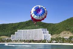 Actividad de la playa: el parasailing, barco de alta velocidad tira de una muchacha en un p imagenes de archivo