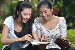 Actividad de las muchachas: compartimiento de la lectura al aire libre Fotos de archivo