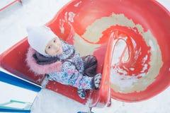Actividad del invierno de la niña en diapositiva plástica espiral del patio Foto de archivo libre de regalías