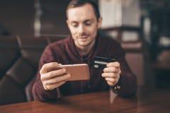 Actividades bancarias en línea con el teléfono elegante, número de la reescritura de la tarjeta de crédito foto de archivo