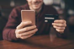 Actividades bancarias en línea con el teléfono elegante, número de la reescritura de la tarjeta de crédito imágenes de archivo libres de regalías