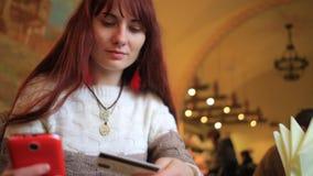 Actividades bancarias en línea de la mujer hermosa usando el smartphone que hace compras en línea con la tarjeta de crédito en la almacen de video