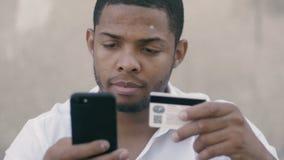 Actividades bancarias en línea del hombre africano joven usando el smartphone que hace compras en línea con la tarjeta de crédito almacen de metraje de vídeo