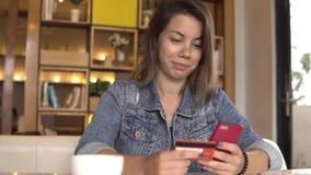 Actividades bancarias en línea Mujer joven que hace compras en línea con la tarjeta de crédito almacen de metraje de vídeo
