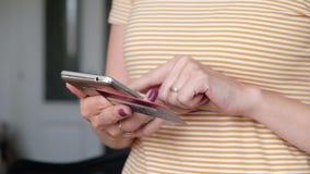 Actividades bancarias en l?nea con el tel?fono elegante Paga fácil usando el teléfono elegante Mujer que hace compras en l?nea co metrajes