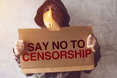 Activist holding Say No To Censorship protest sign. Hooded activist protestor holding Say No To Censorship protest sign. Man with hoodie and scarf over face royalty free stock image
