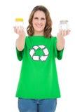 Activista ambiental sonriente que muestra los potes que miran la cámara Imagen de archivo libre de regalías