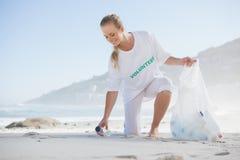 Activista rubio que coge basura en la playa Imagenes de archivo