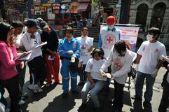 Activists of the red cross teach people first aid on a city street. Stock Photo