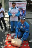 Activists of the red cross teach people first aid on a city street. Stock Images