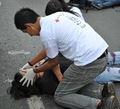 Activists of the red cross teach people first aid on a city street. Royalty Free Stock Images