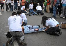 Activists of the red cross teach people first aid on a city street. Royalty Free Stock Photography