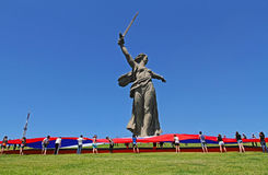 Activists unfurl a large Russian flag in Day of Russia at the foot of the monument of Motherland Calls on Mamaev hill in Volgograd. Volgograd, Russia - June 12 Royalty Free Stock Image