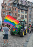 Activists waving flag. Activists waving the rainbow flag in front of a tractor in Stortorget Stock Photos
