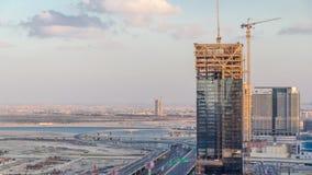 Activité de construction dans le centre ville de Dubaï avec le timelapse de grues et de travailleurs, EAU banque de vidéos