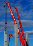 Activité de construction Deux grues télescopiques et récolteuses d'une cerise installent les premières colonnes structurelles con Photos libres de droits