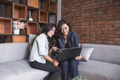 Activité femelle de deux amis utilisant l'ordinateur portable Photos stock