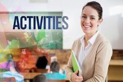 Activités contre le joli professeur souriant à l'appareil-photo au dos de la salle de classe photos stock