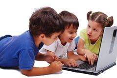 Activités de Chidren sur l'ordinateur portatif d'isolement dans le blanc Image libre de droits