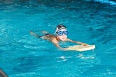 Activités sur la jeune forme physique de natation de garçon de piscine Image stock
