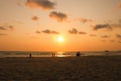 Activiteit op het strand in zonsondergangtijd het silhouet van mensen op is Stock Foto's