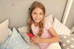 Activiteiten voor pyjamapartij Van de de slijtagepyjama van het meisjesjonge geitje de greepsmartphone Kind in smartphone van de  stock foto
