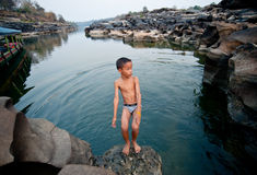 Activities on the mekong river, children swimming and playing rock holes Stone Royalty Free Stock Images
