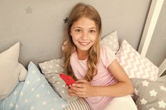Activities for pajama party. Girl kid wear pajama hold smartphone. Child in pajama hold smartphone. Pajama party ideas. Girl surfing web searching ideas for stock photo