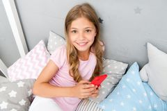 Activities for pajama party. Girl kid wear pajama hold smartphone. Child in pajama hold smartphone. Pajama party ideas. Girl surfing web searching ideas for royalty free stock image