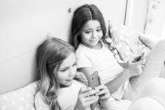 Activities for pajama party. Girls kids best friends or sisters wear pajama busy with smartphones. Children in pajama. Interact with smartphones. Technologies royalty free stock photo